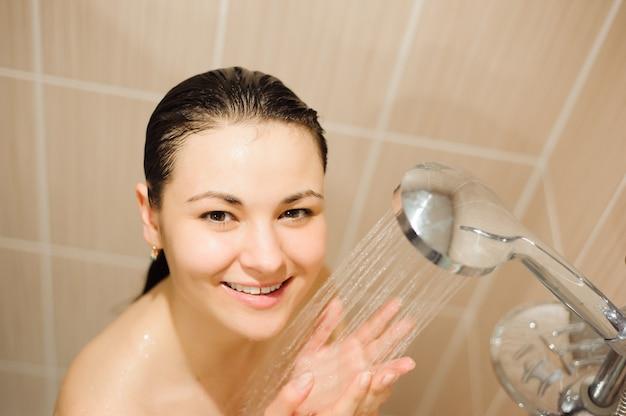 シャワーを持つ美しい女性