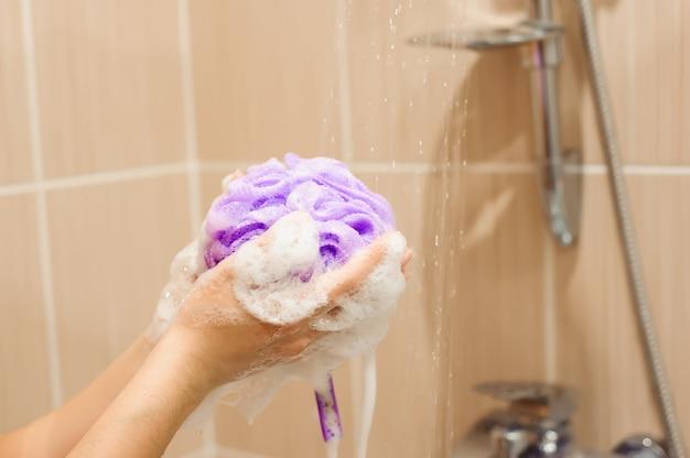バスルームでシャワーを浴びながら石鹸を使用する女性