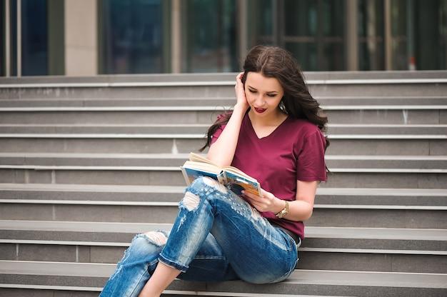 建物の階段で本を読んで美しい女性