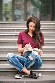 座って本を読む若いきれいな女性は、残りの部分を楽しんでいます。