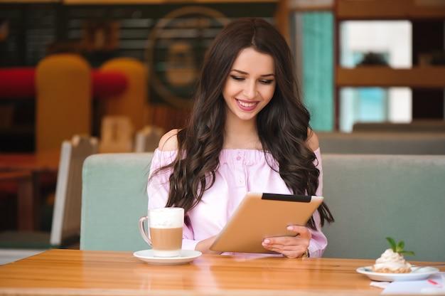 コーヒーショップでのタブレットの女性の使用