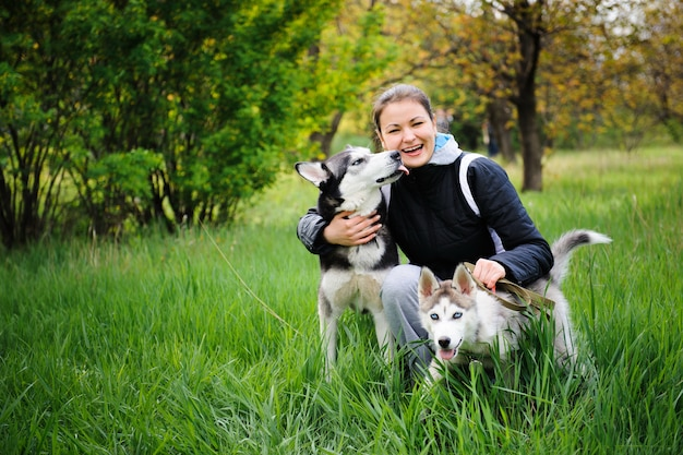 少女と彼女の犬ハスキーが公園を散歩