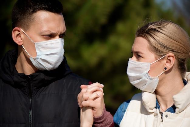 Друзья в масках гуляют по парку, опасаясь заразиться коронавирусом.