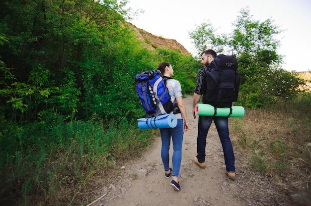 Молодая пара туристов в лесу. спортивный мужчина и женщина с рюкзаками на дороге в природе.