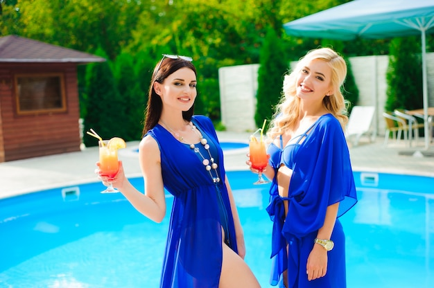 Две счастливые девушки отдыхают у бассейна с коктейлями.