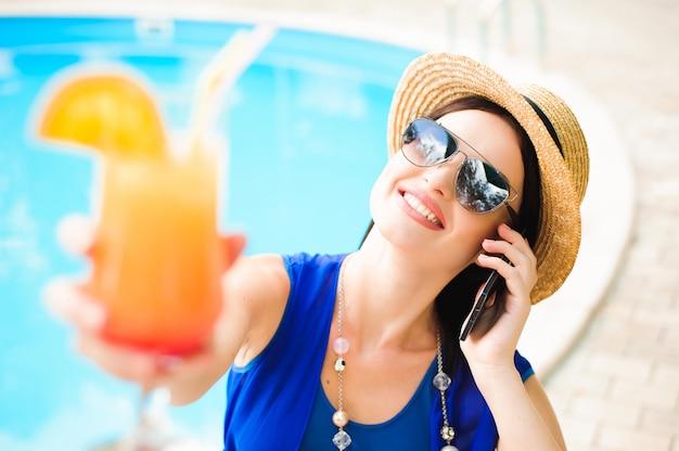 スイミングプールのそばの電話と美しい若い女性