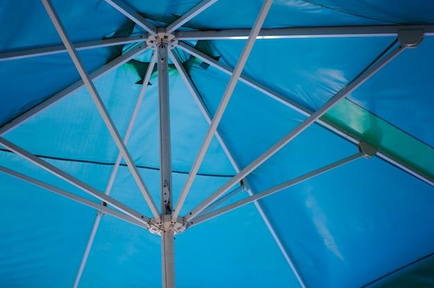 太陽の保護としての青いビーチパラソル