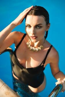 ファッションビキニでセクシーなフィットの体を持つ女性、プールの水から出てくる水着
