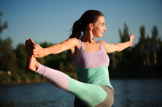 Закройте вверх молодой женщины делая йогу в парке с заходом солнца.