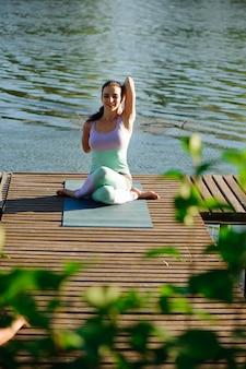 Йога в парке, на открытом воздухе с эффектом света, здоровье женщины, йога женщина. концепция здорового образа жизни и отдыха