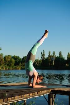 健康な女性のライフスタイルは、朝の自然の中で橋の上で瞑想とエネルギーヨガの練習のバランスをとっています。