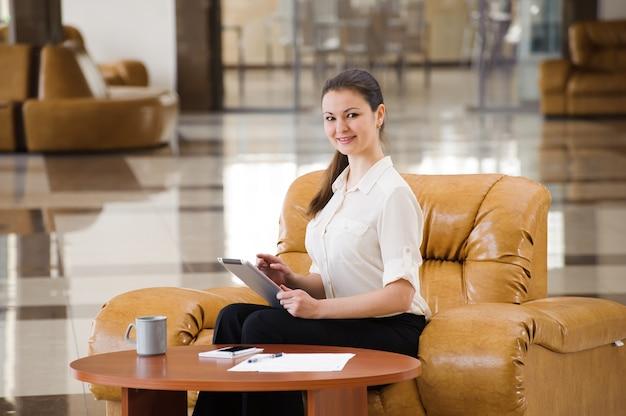 Портрет занятой бизнес-леди работая пока сидящ на софе.