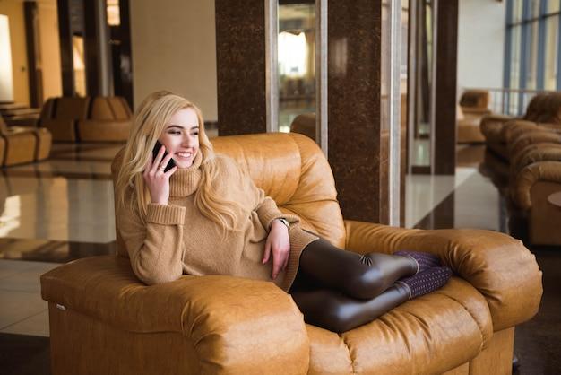 魅力的な女性は彼女の携帯電話を使用してコーヒーブレークを持っています
