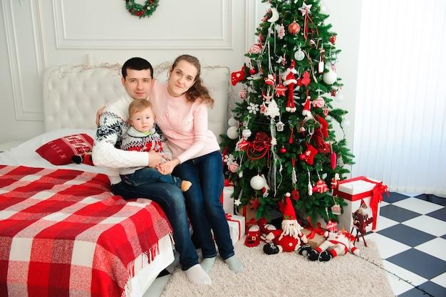 家族のクリスマスツリーでポーズ
