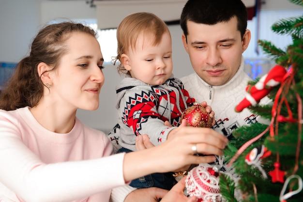 Родители с дочкой наряжают елку.