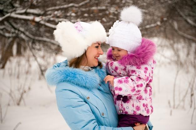 Мать и ее маленькая дочь, наслаждаясь красивый зимний день на открытом воздухе.