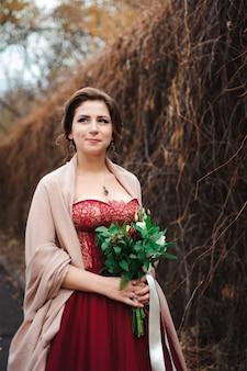 手にウェディングブーケを持つ赤いドレスを着た美しい花嫁の肖像画