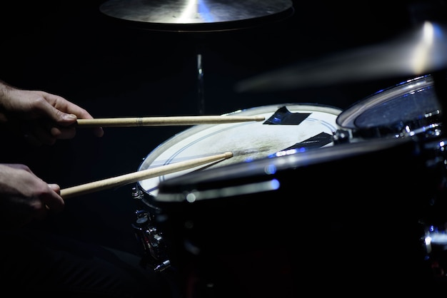 男はスティックのクローズアップ、ワーキングドラム、ステージ上の美しい照明と音楽のコンセプトを持つ音楽打楽器を演奏します。