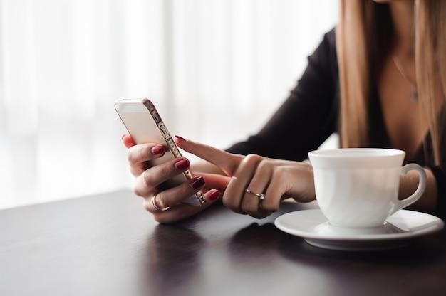レストラン、カフェで彼女の携帯電話を使用して手の女性のクローズアップ。