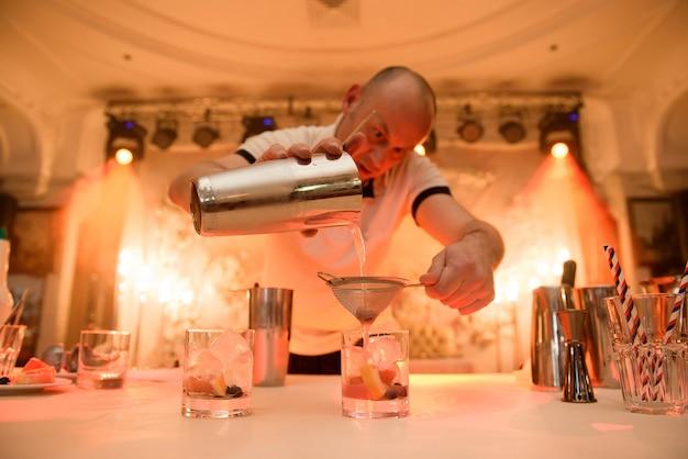 バーテンダーがバーのカウンターでウイスキーのカクテルにカクテルの材料を追加します。