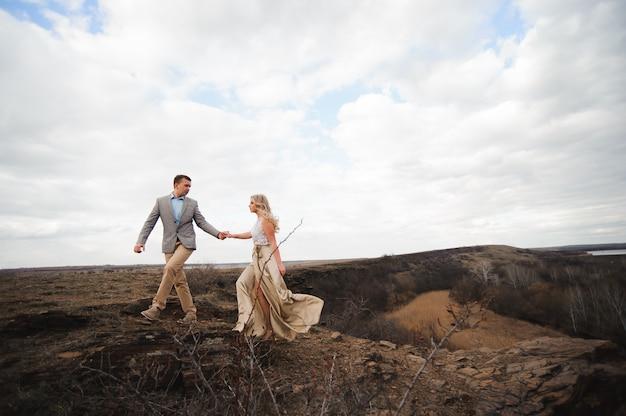 Красивый парень и блондинка гуляют по полю, мужчина ведет женщину, держащую за руку.