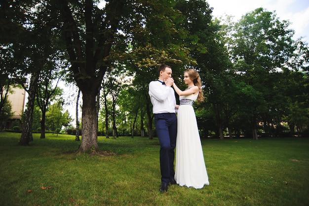 結婚式の日。自然の場所で屋外の新郎新婦。結婚式の日に愛の結婚式のカップル