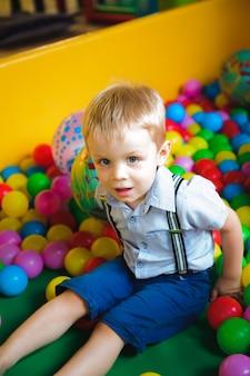 ボールを持って子供たちの迷路の遊び場で遊ぶ男の子。マルチカラーのボール