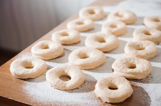 シェフが生地を準備しています。ドーナツの調理プロセス、小麦粉での作業。