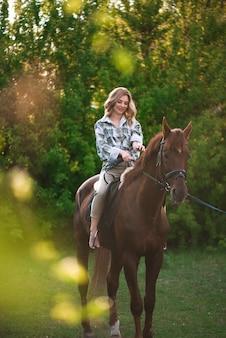 Женщина с длинными волосами, позирует с коричневой лошадью в лесу в солнечный луг.