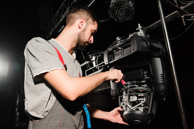 Инженер по свету регулирует свет на сцене