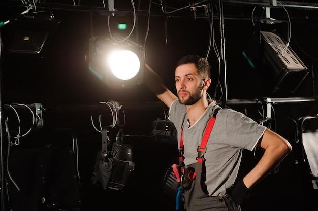 Рабочий на сцене устанавливает огни. инженер по свету регулирует свет на сцене за кулисами