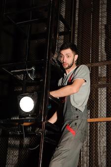 Инженер по свету регулирует свет на сцене за кулисами.
