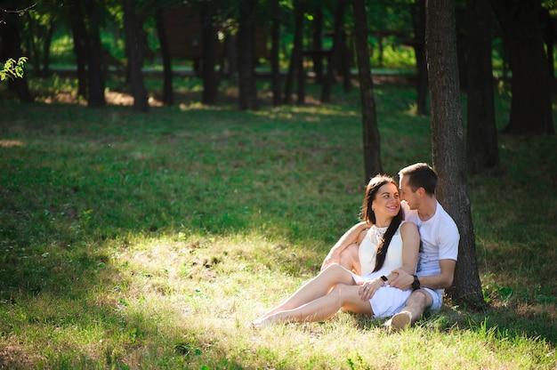 美しいカップルは、庭の大きな木の近くに座って、街の外で休んでいます。ラブストーリー