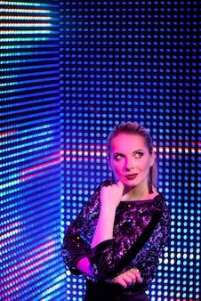 ネオンの光の中でモデルの女性。紫外線でポーズをとる女性のディスコダンサーのアートデザイン。ネオンの背景に分離されました。