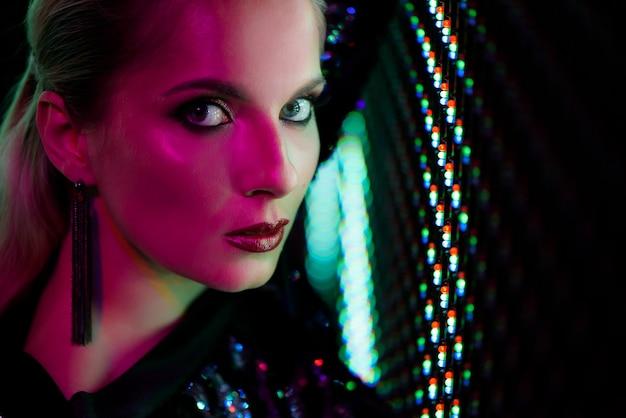 Фасонируйте фото сексуальной девушки одетой в черноте в ночном клубе. ночной клуб девушка неоновые концепции.