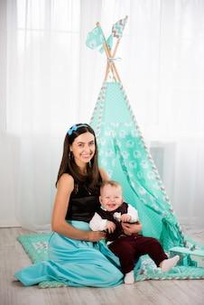 美しい女性と彼女の幼い息子が遊んでいると笑顔
