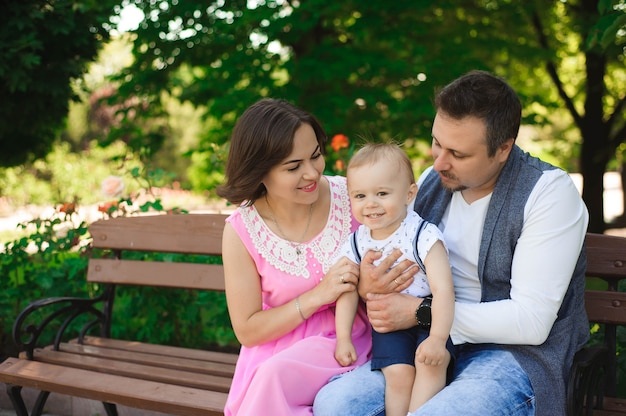 Концепция семьи, родительства, принятия и людей - счастливая мать, отец и мальчик идя в лето паркуют.