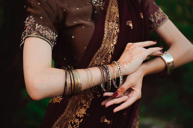 黒の一時的な刺青の入れ墨を持つ女性の手。黒のヘナの入れ墨を持つインドの花嫁の女性の手。ファッション。インド