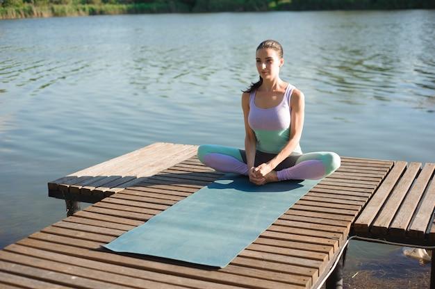 Женская йога - отдых на природе. кавказская женщина йога на мосту, медитации в позе йоги на горном ручье.