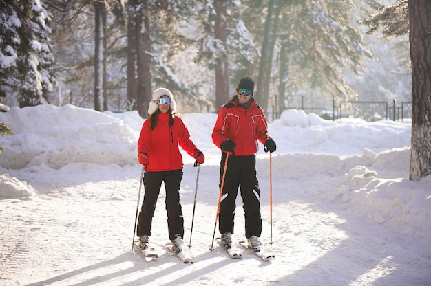 Катание на лыжах, снег, зимние развлечения, счастливая семья катается на лыжах в лесу.