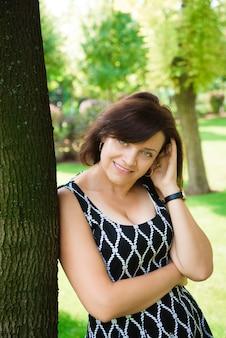 Счастливая старшая женщина ослабляя и усмехаясь внешняя в летнем дне.