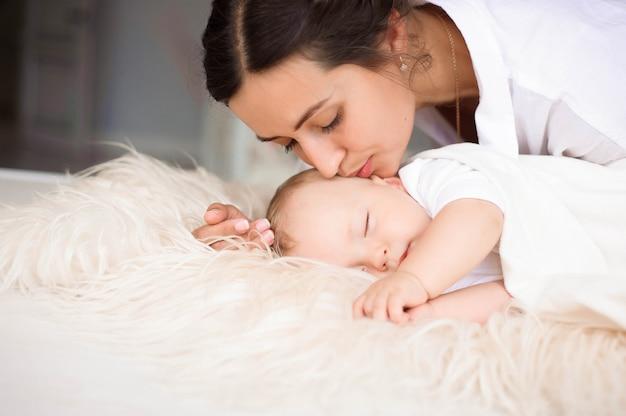 彼女の生まれたばかりの赤ちゃんを優しく保持している若い母親