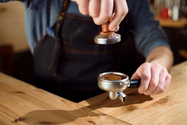 バリスタはコーヒーショップでタンパーを使用して挽いたコーヒーを押します