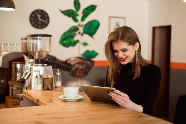 カフェでタブレットコンピューターを使用して若い女性。