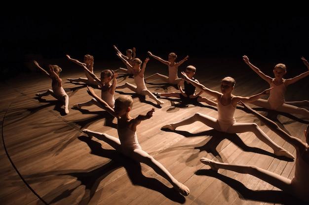 かなり若い女の子と男の子がストレッチとバレエダンスのトレーニングを持つステージに座っています。