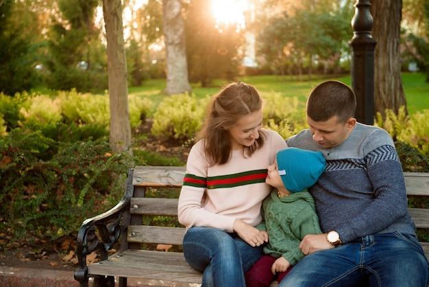 幸せな家族母父と秋の赤ちゃんは公園で散歩します。