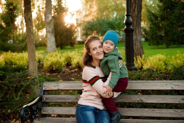 Молодая мама и ее малыш-мальчик веселятся осенью