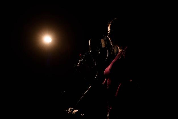 音楽スタジオで歌を録音する歌手。