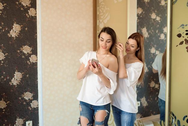 Две красивые улыбающиеся сестры или подруги собираются на вечеринку и делают друг другу прически у себя дома.