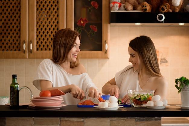 家族の家庭の台所で双子と野菜を刻んで若いガールフレンド。